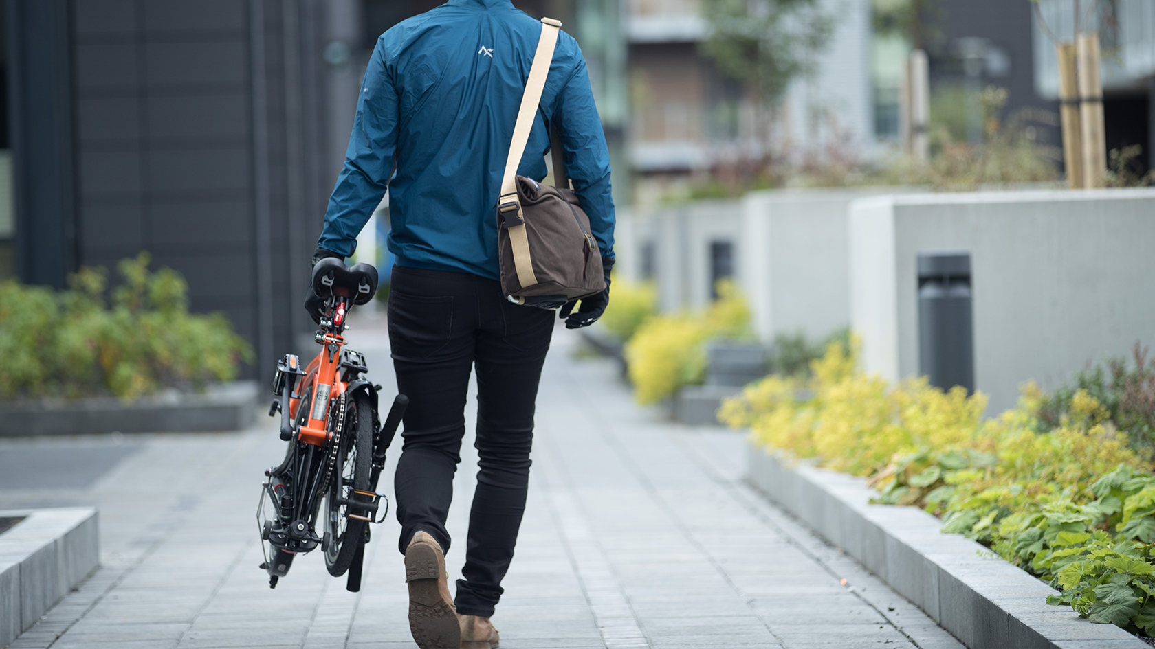 Man carrying a folded Brompton bike with Brompton Roll Top Shoulder Bag
