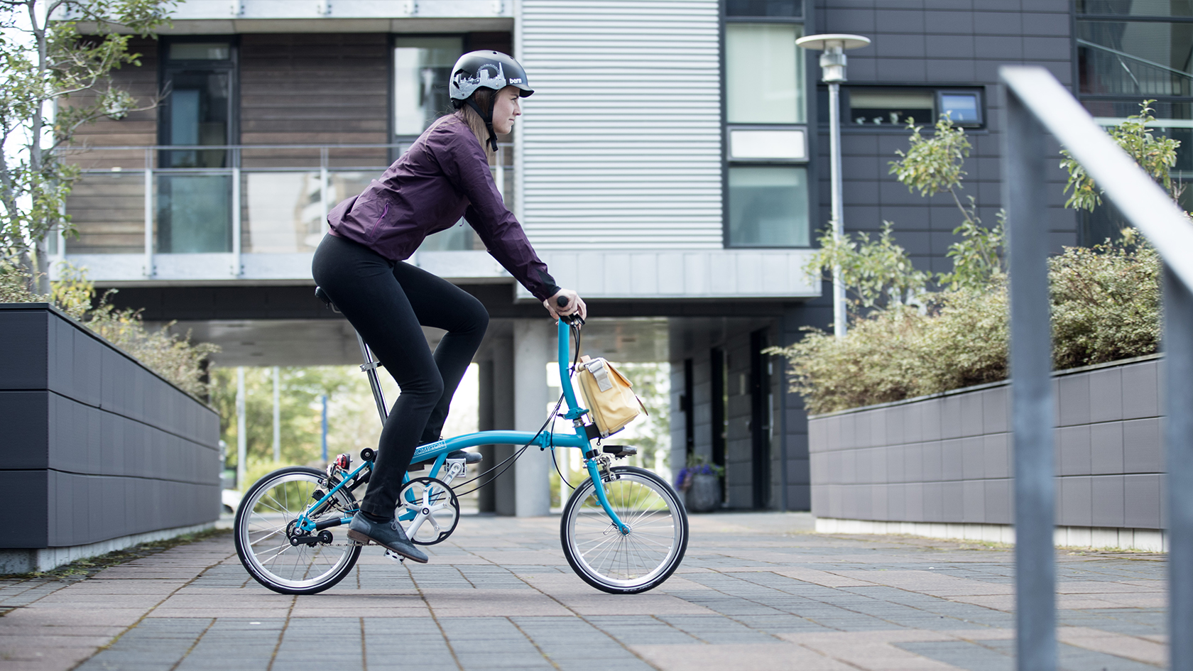 Lady riding a blue Brompton bike with S-type handlebars.